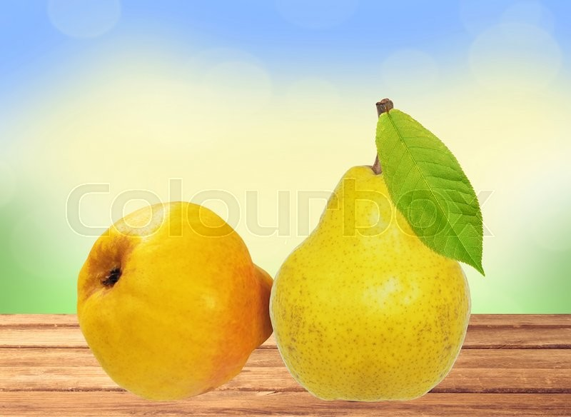 Two sweet pears on wooden table over bright nature background, stock photo