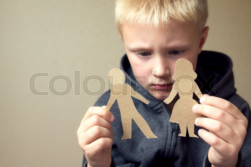 Confused child with cutting paper parents, family problems, divorce, custody battle, suffer concept , stock photo