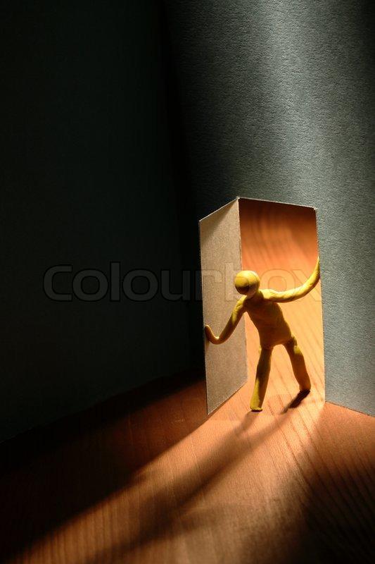 Yellow plasticine man entering to dark room Conceptual