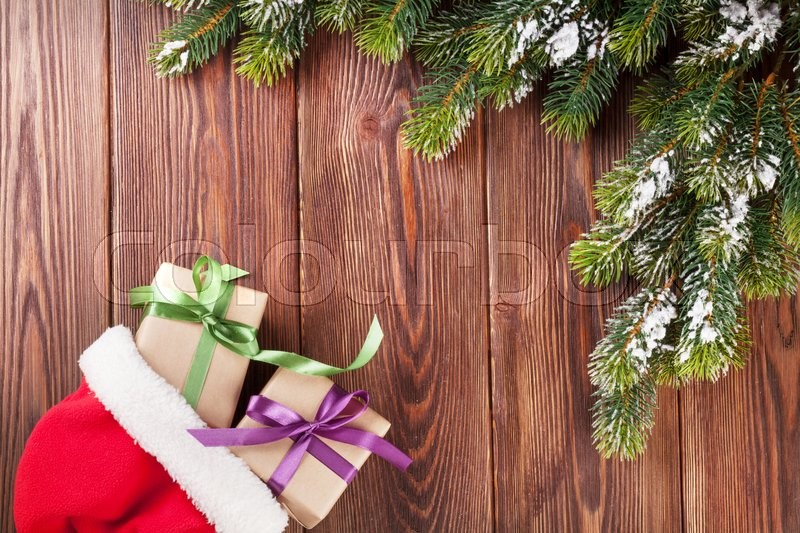 Christmas tree branch and santa hat with gift boxes on wooden table. Top view with copy space, stock photo