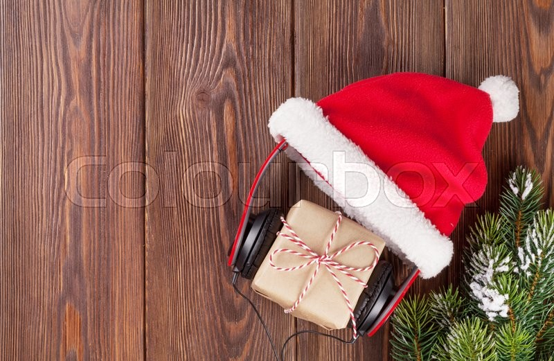 Christmas gift box with headphones and santa hat on wooden table. Top view with copy space, stock photo