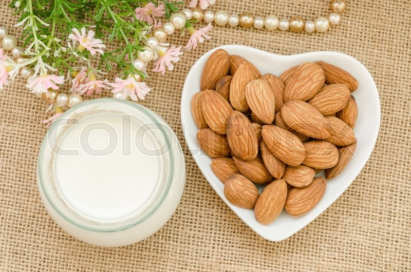 Almond milk with almond on a white bowl cup with flower on sack background, stock photo