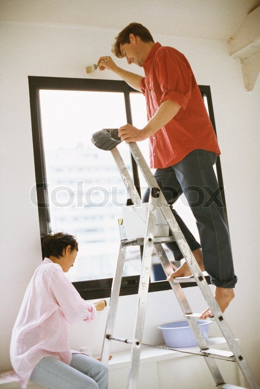John Dowland AltoPress Maxppp Couple Painting Wall Together Man Standing On Ladder Stock Photo