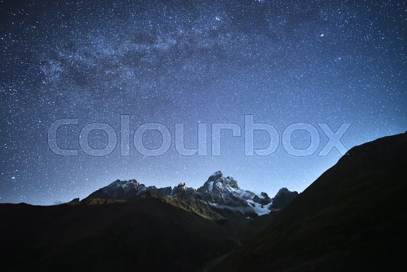Night landscape. Starry sky with the Milky Way over the mountains. Mount Ushba in the light of the rising moon. Main Caucasian ridge. Zemo Svaneti, Georgia , stock photo
