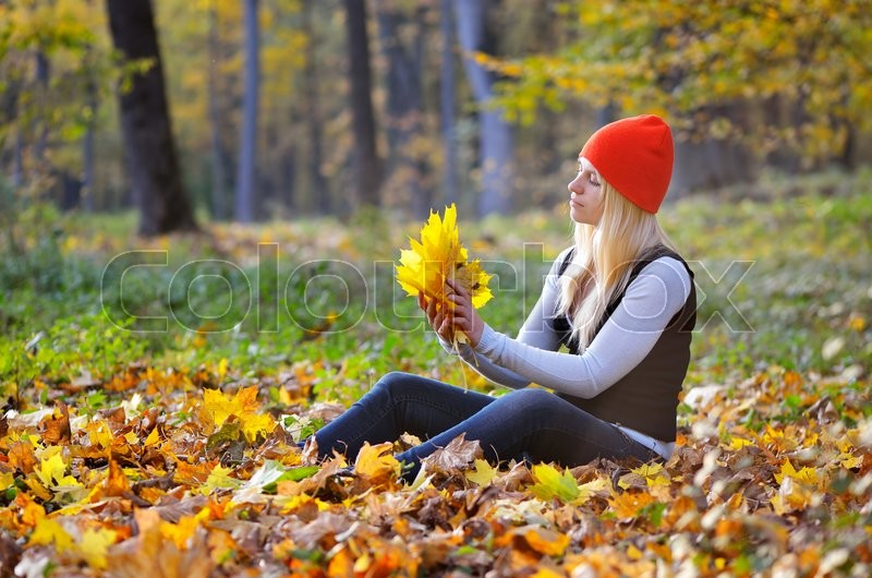 Blonde girl in the autumn park gathers a bouquet of maple leaves, stock photo