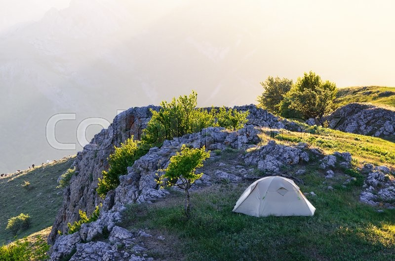 Spring landscape with tourist tent. Camping in the mountains of the Solar spring day, stock photo