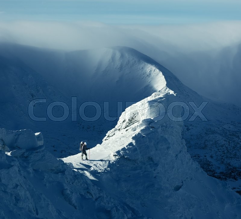 Winter landscape. Sunny day in the mountains. Tourist standing on a rock, stock photo