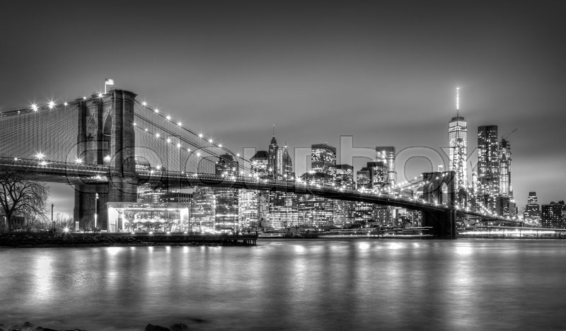 Brooklyn bridge and New York City Manhattan downtown skyline at dusk with skyscrapers illuminated over East River panorama. Copy space. Black and white image, stock photo