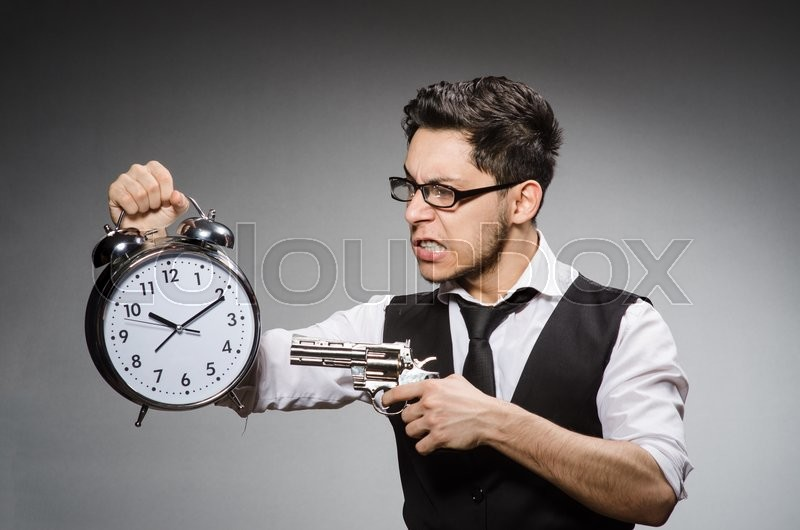 The employee holding alarm clock and handgun against gray, stock photo