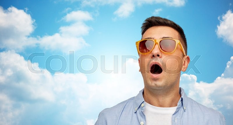 Summer, emotions, style and people concept - face of scared or surprised middle aged latin man in shirt and sunglasses over blue sky and clouds background, stock photo