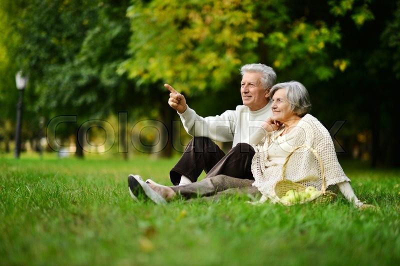 Beautiful caucasian elderly couple in the park in autumn, stock photo