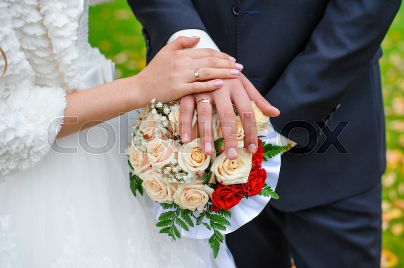 Bridal bouquet close up in the hands of the bride and groom, stock photo
