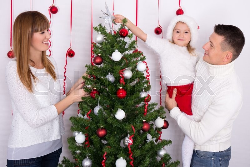 Young happy family decorating Christmas tree at home, stock photo