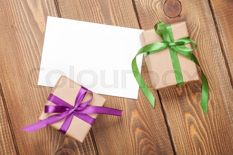 Photo frame card and gift boxes with ribbon over wooden table background, stock photo