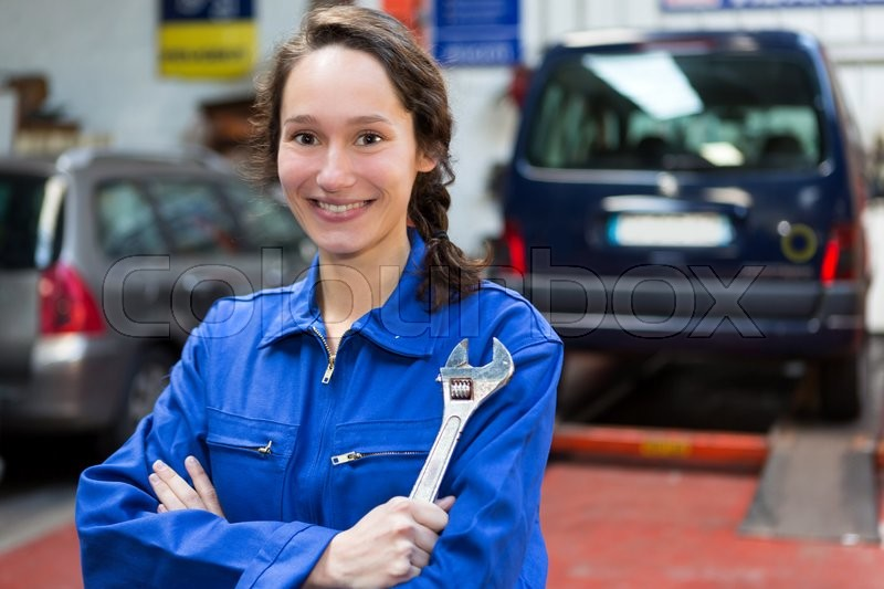 View of a Young attractive woman mechanic working at the garage, stock photo