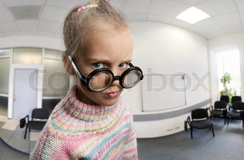 Stock image of 'Serious little girl in glasses in the class'