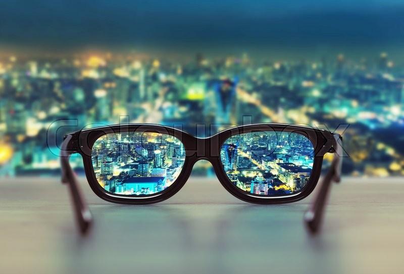 Night cityscape focused in glasses lenses. Vision concept, stock photo