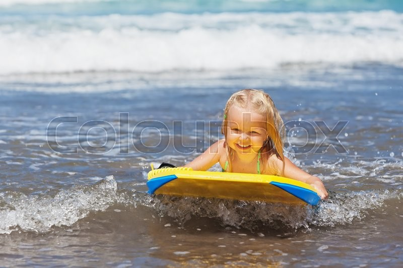 Little baby girl - young surfer with bodyboard has a fun on small sea waves. Active family lifestyle, people outdoor water sport lessons and swimming activity on surf camp summer vacation with child, stock photo