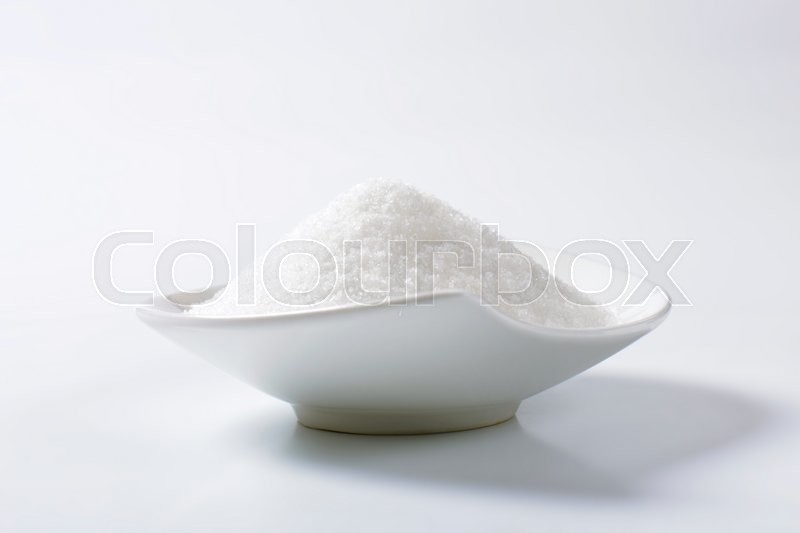 Heap of crystal sugar in white bowl, stock photo