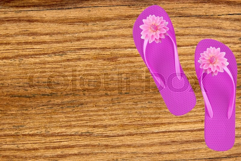 Pink beach shoes with flowers on wooden background, stock photo
