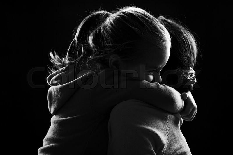 Black and white image of a little girl hugging her mother, stock photo