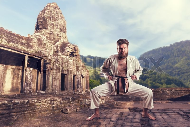Fat karate fighter in white kimono in karate stance, stock photo
