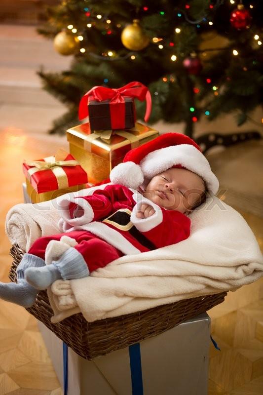 cute baby boy in santa costume sleeping under christmas tree stock photo colourbox