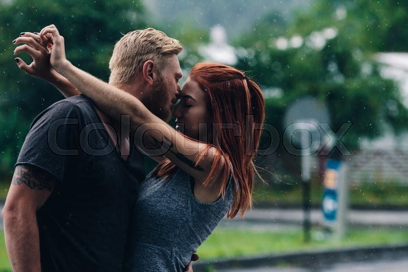 Beautiful couple kissing outside in the rain, stock photo