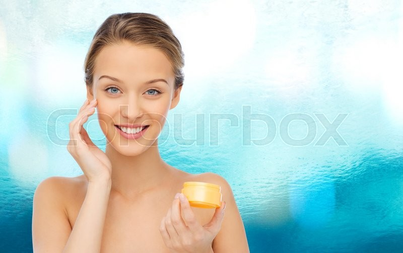 Beauty, people, cosmetics, skincare and cosmetics concept - happy young woman applying cream to her face, stock photo