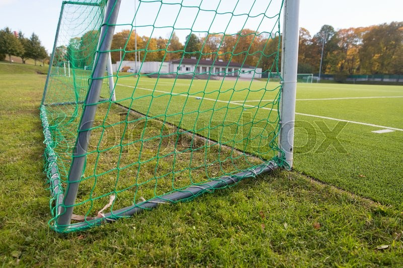 Sport and equipment concept - close up of football goal on field, stock photo