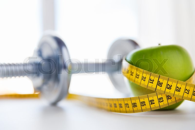 Sport, fitness, diet and objects concept - close up of dumbbell and green apple with measuring tape, stock photo
