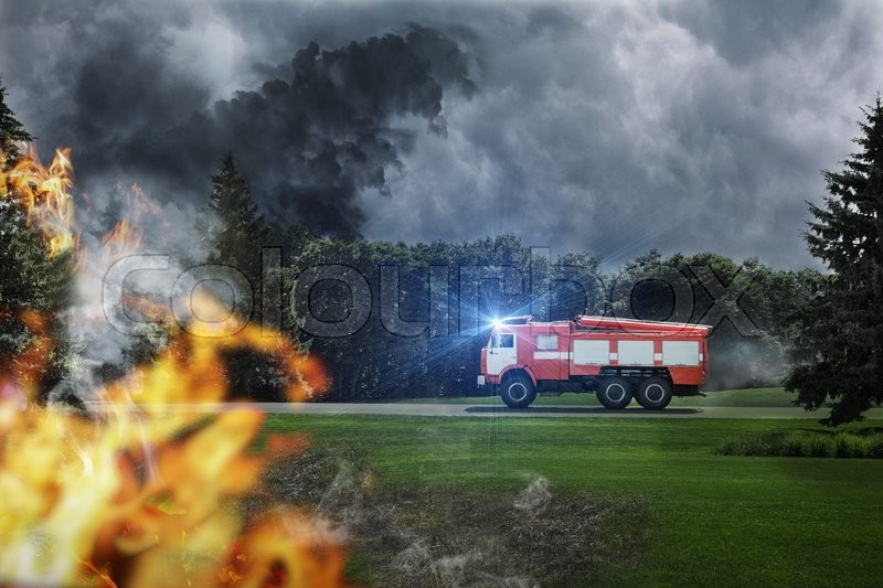 Fire-engine is in hurry to extinguish dangerous fire in the forest, stock photo