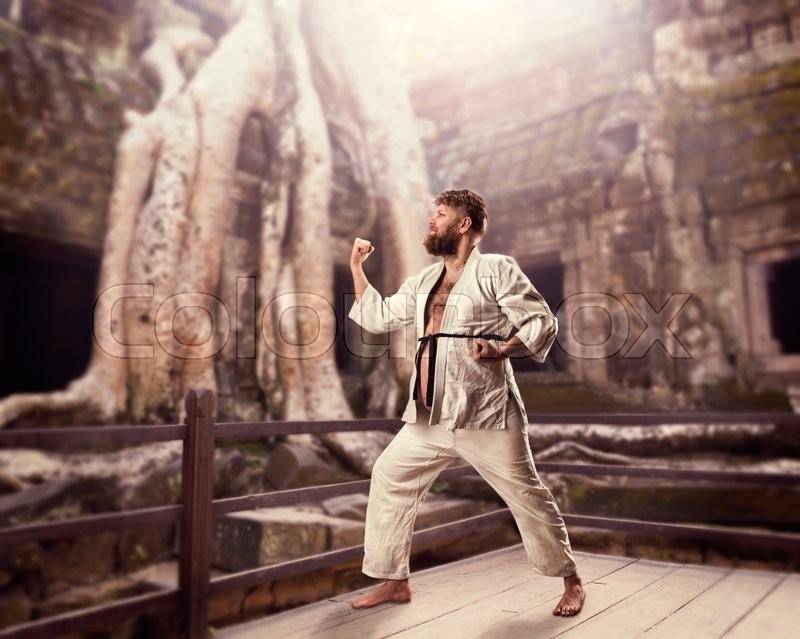 Fat bearded karate fighter in white kimono doing kata against temple, stock photo