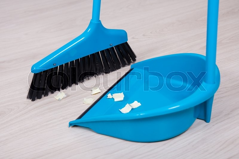 close up of broom and dustpan with paper trash on wooden floor stock photo colourbox