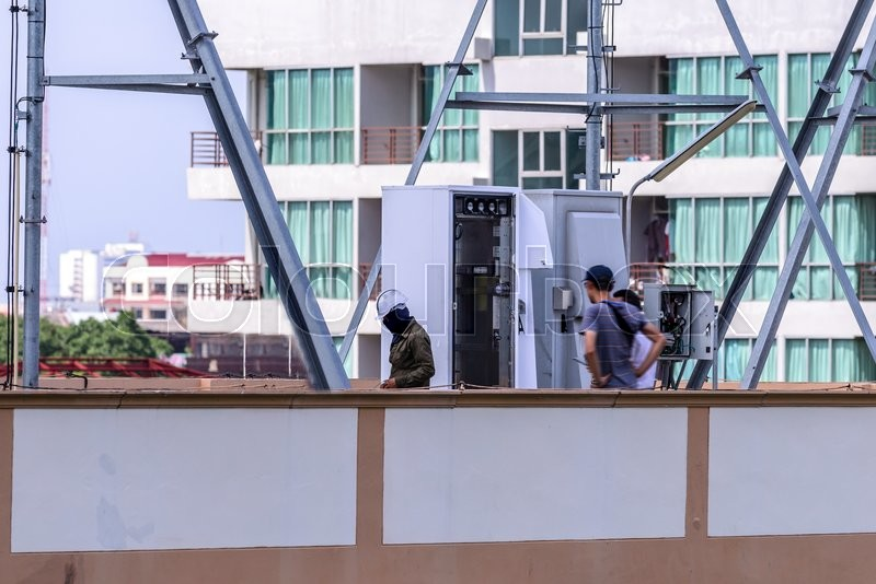 Technician support installing internet cable in controller box on the roof, stock photo