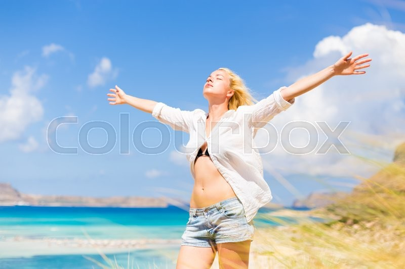 Relaxed woman enjoying freedom and life an a beautiful sandy beach. Young lady raising arms, feeling free, relaxed and happy. Concept of freedom, happiness, enjoyment and well being, stock photo