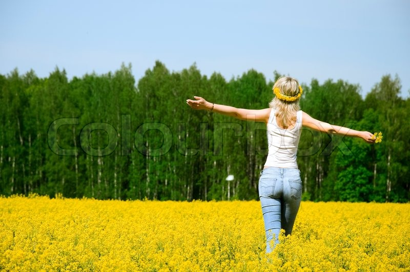 Happy young woman is standing on a flower field | Stock ...