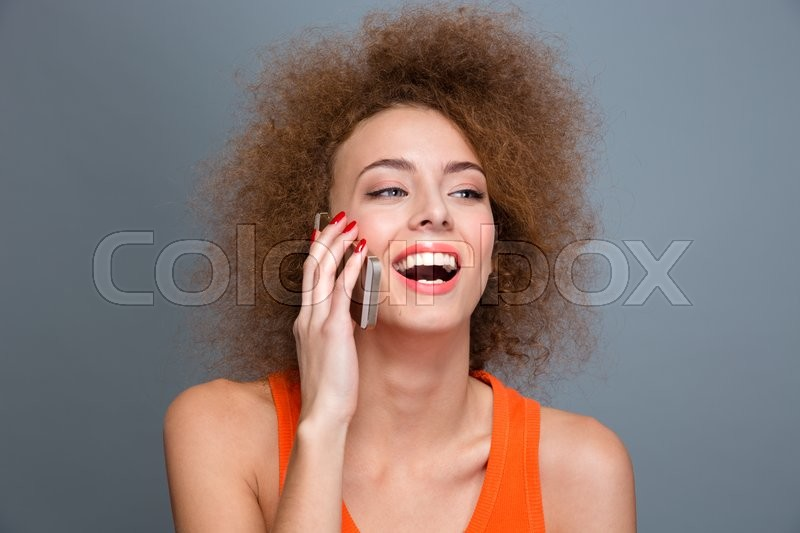 Happy delightful beautiful flirty curly woman talking on mobile phone and laughing, stock photo