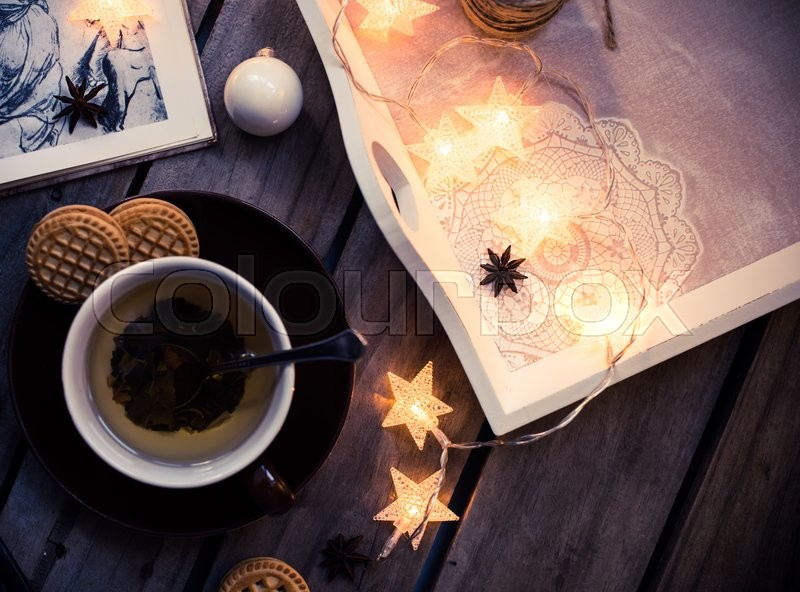 Winter holiday background: cup of tea, Christmas lights and other home decoration on vintage wooden table. Cozy holidays at home, stock photo
