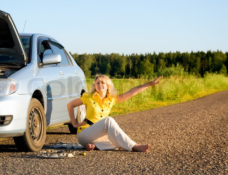 Girl standing by the side of the road with the hood of her car open signaling problems with the car, stock photo