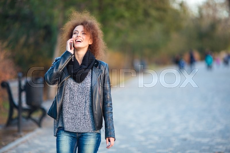 Portrait of a laughing woman walking and talking on the phone outdoors , stock photo