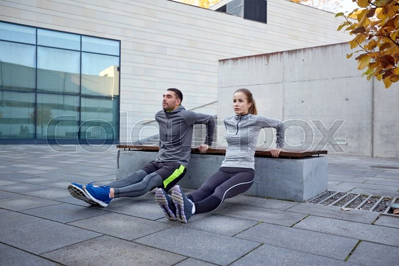Fitness, sport, training, people and lifestyle concept - couple doing triceps dip exercise on bench outdoors, stock photo