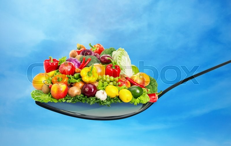 Spoon full of various fruit and vegetables on blue sky, stock photo
