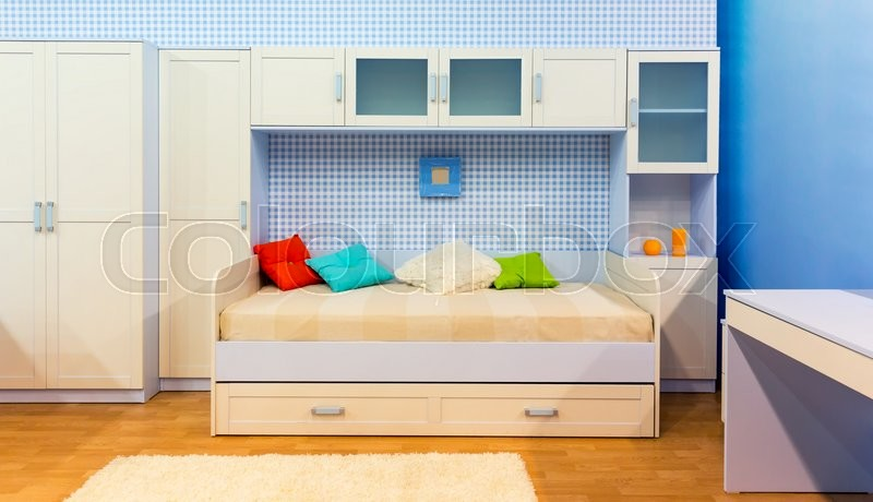 Bright bedroom with a bed with pillows and cupboard, stock photo