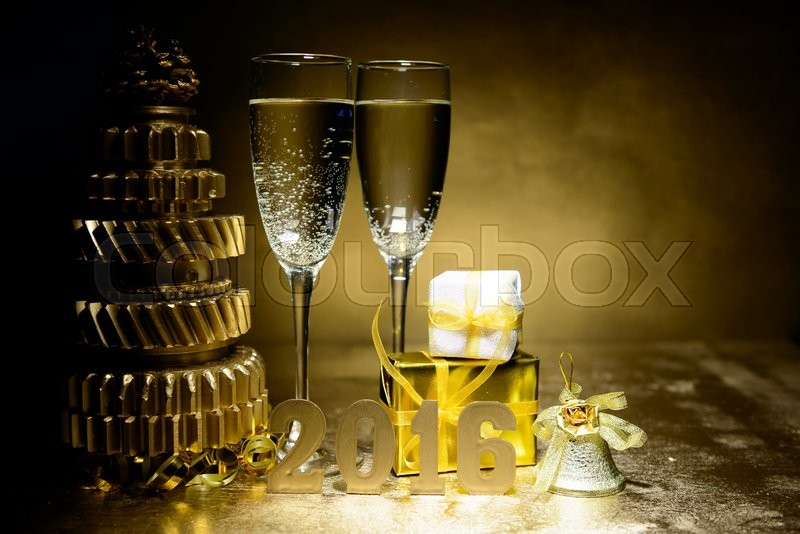 New Year composition with champagne and gifts on gold background, stock photo