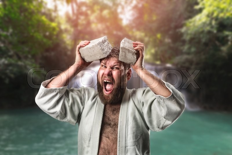 Strong karateka breaks a brick on his head, stock photo