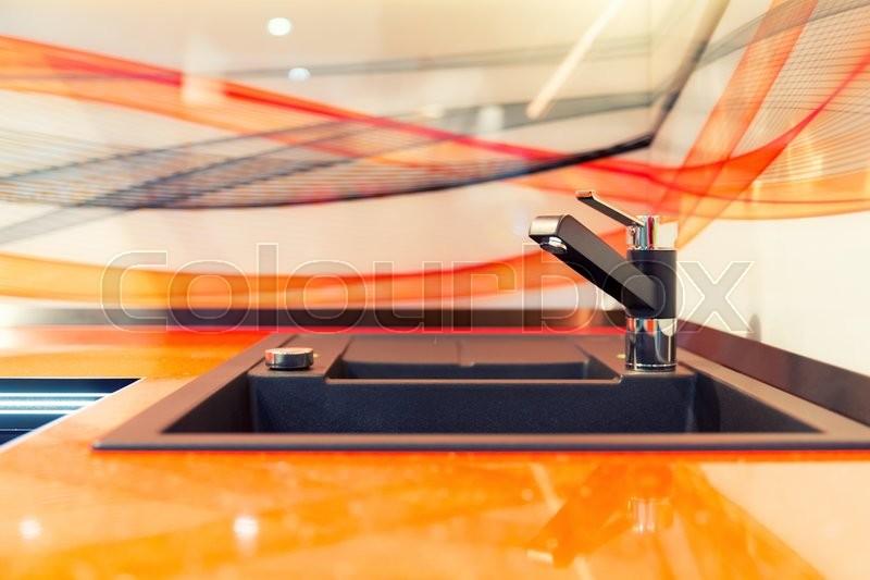Modern kitchen sink in orange ceramic closeup, stock photo