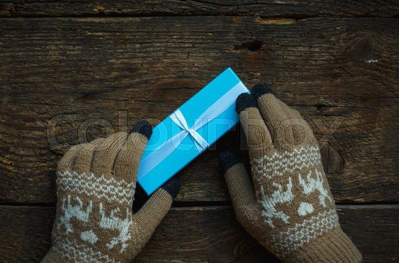 Female hands in winter gloves with christmas gift box on wooden background, stock photo