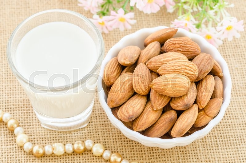 Almond milk in glass and almonds in white cup with flower on sack background, stock photo