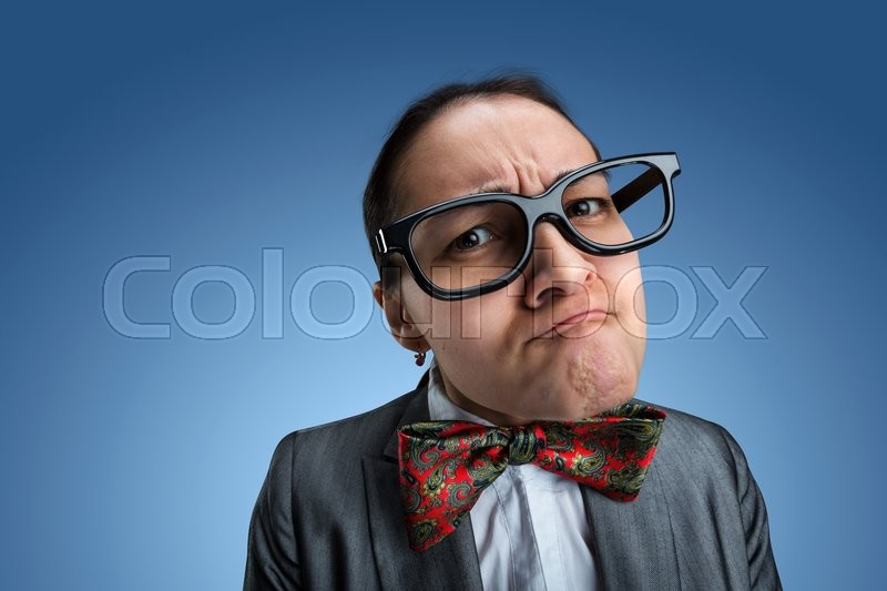 Funny nerd girl in glasses looks at you over blue background, stock photo
